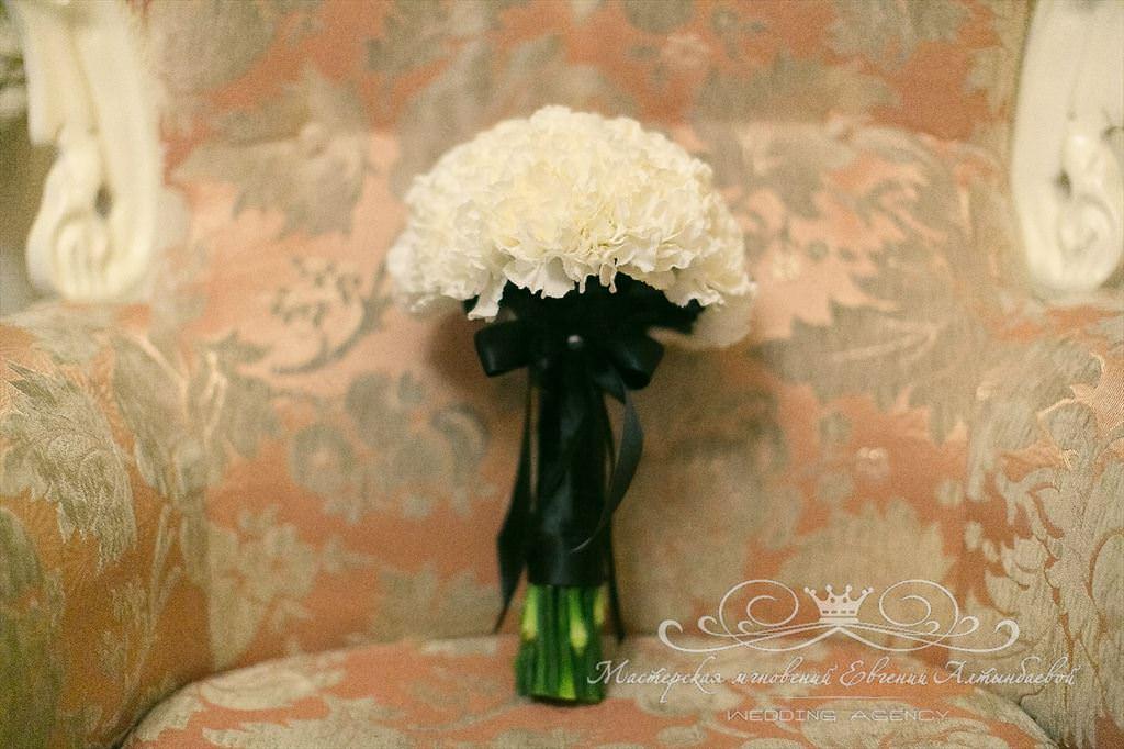 Букет невесты из белых гвоздик, декорированный чёрной атласной лентой